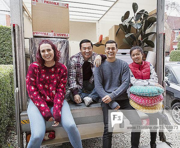 Portrait happy friends at back of moving van