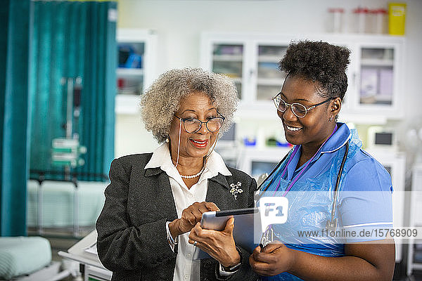 Female doctor and nurse using digital tablet in hospital