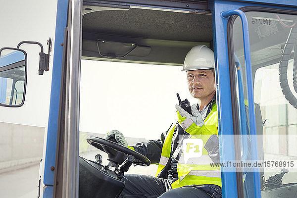 Dock worker using walkie-talkie and operating crane at shipyard