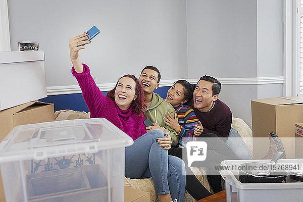 Happy friends taking a break from moving  taking selfie on sofa