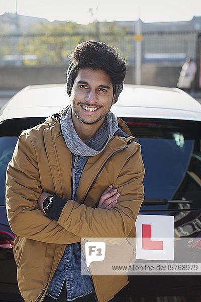 Porträt eines selbstbewussten jungen Mannes mit Führerschein  der sich an ein Auto lehnt