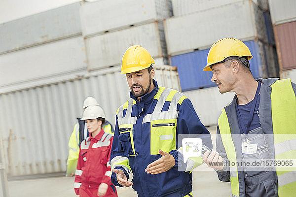 Dock workers walking and talking at shipyard