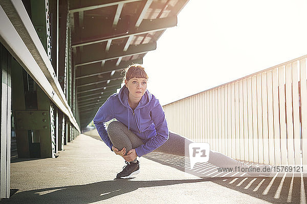 Focused young female runner stretching legs on sunny train station platform