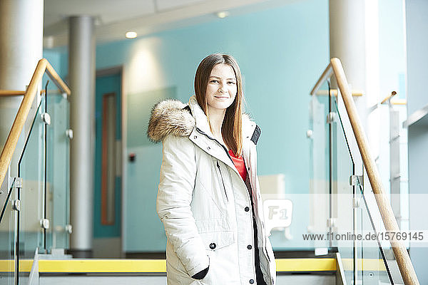 Portrait confident young female college student wearing coat