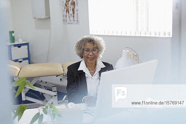 Porträt einer lächelnden  zuversichtlichen älteren Ärztin  die in einer Arztpraxis am Computer arbeitet