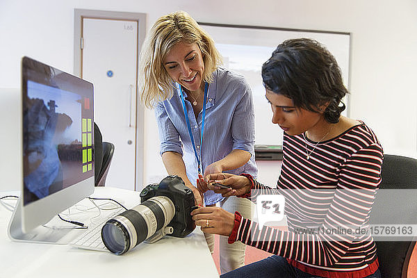 Female photographer teaching student how to use SLR camera