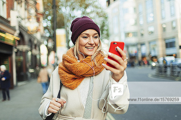 Young woman with headphones and smart phone video chatting on autumn street