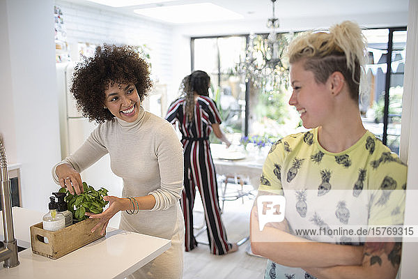 Happy young women talking in kitchen