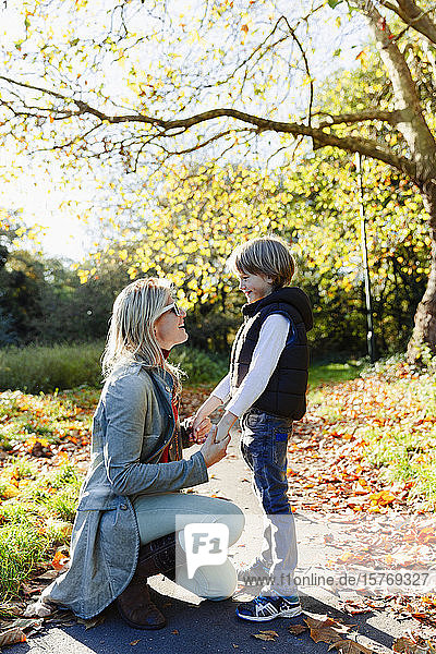 Mother and son holding hands and talking in sunny autumn park