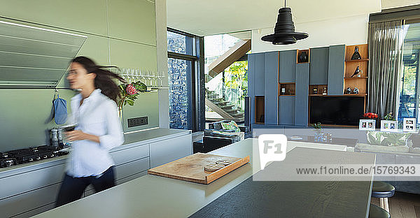 Woman walking in modern kitchen