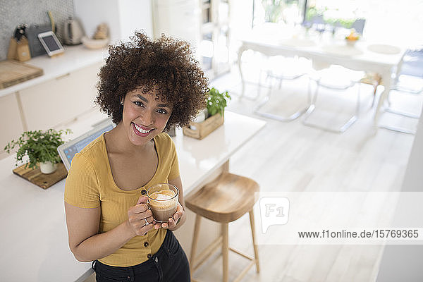Portrait happy young woman drinking cappuccino in kitchen