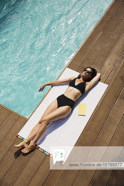 Sensual woman in black bikini sunbathing at sunny summer poolside