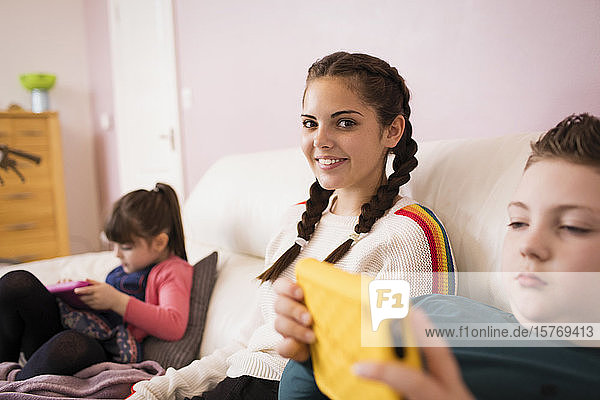 Portrait confident teenage girl on sofa with siblings