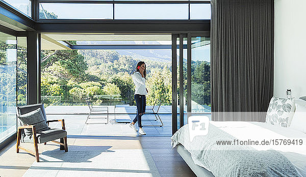 Woman talking on smart phone in patio doorway of modern  luxury bedroom