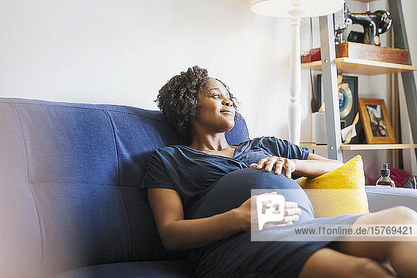 Serene pregnant woman relaxing on sofa