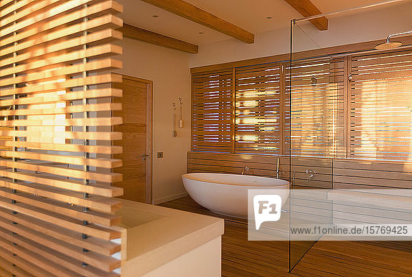 Soaking tub and shower surrounded by wood in modern  luxury home showcase interior bathroom