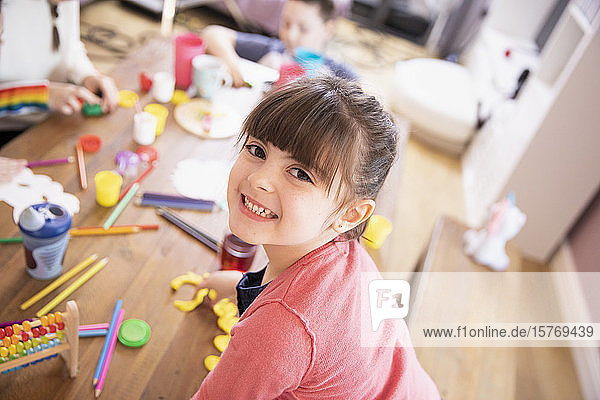 Portrait happy enthusiastic girl playing with toys at table