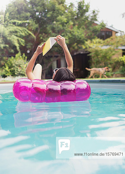 Woman relaxing  reading book on inflatable raft in sunny summer swimming pool