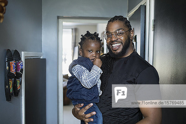 Portrait happy father holding toddler son