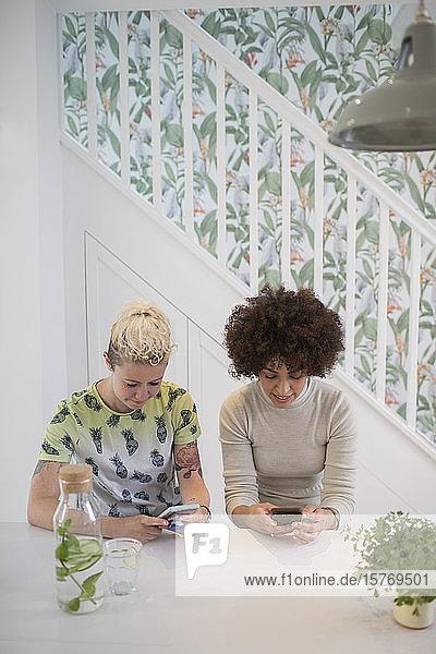 Young women friends using smart phones in kitchen