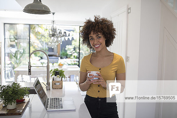 Portrait happy confident young female freelancer working at laptop