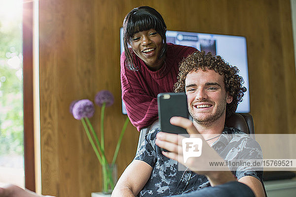 Happy young couple using smart phone