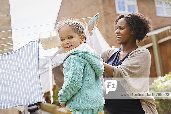 Portrait happy girl helping pregnant mother hang laundry on clothesline