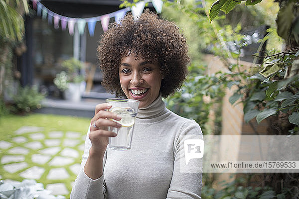 Portrait happy young woman drinking water on patio
