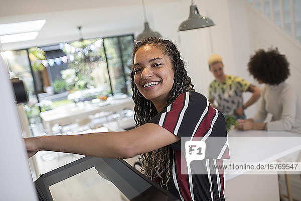 Portrait happy young woman cooking kitchen