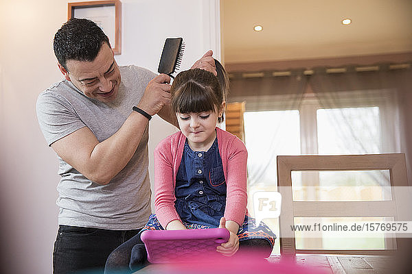Father brushing hair of daughter using digital tablet