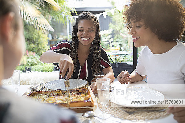 Young women friends slicing homemade pizza in dining room