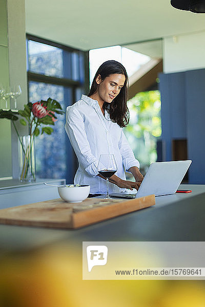 Woman using laptop and drinking red wine in kitchen