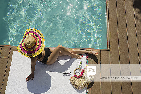 Woman in sun hat sunbathing  relaxing at sunny summer poolside