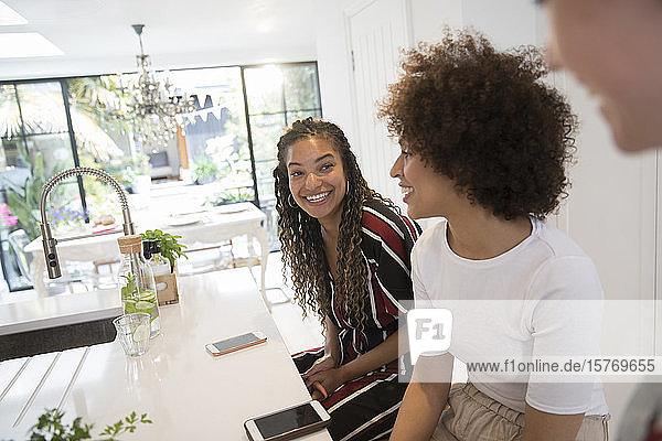 Happy young women friends with smart phones in kitchen