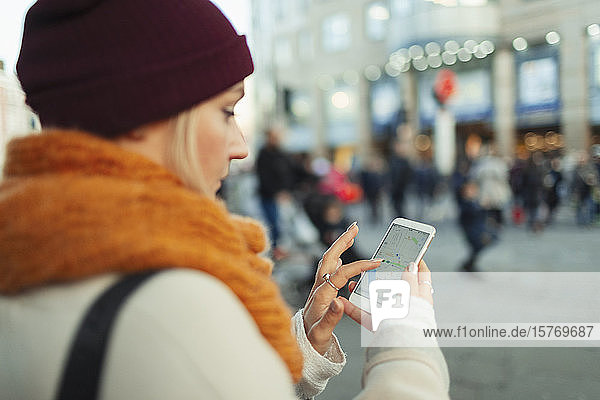 Young woman using GPS on smart phone on urban street