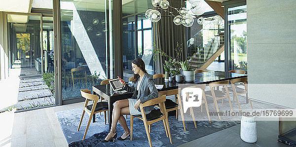 Businesswoman working from home  using smart phone at modern dining table