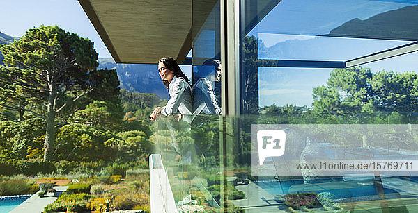 Serene woman on sunny luxury balcony