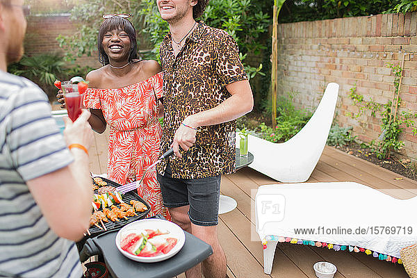 Happy young multiethnic couple barbecuing on summer patio