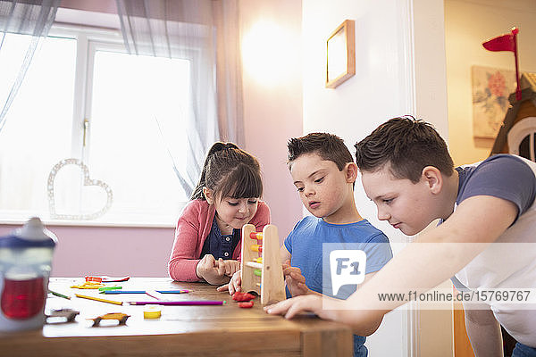 Boy with Down Syndrome and siblings playing with toys at table