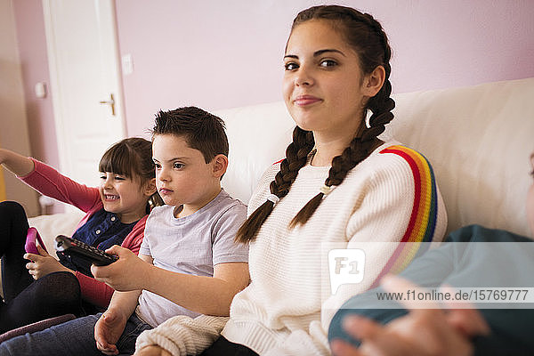 Portrait smiling girl watching TV with siblings on sofa