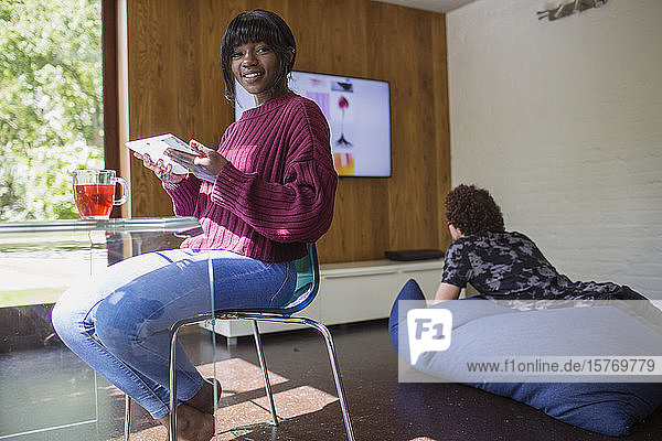 Portrait smiling young woman using digital tablet in living room