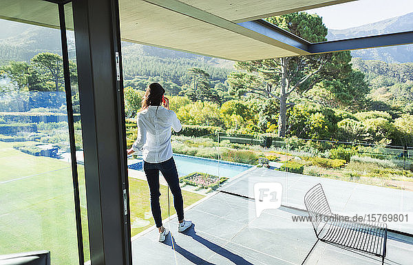 Woman talking on smart phone on sunny luxury balcony with view