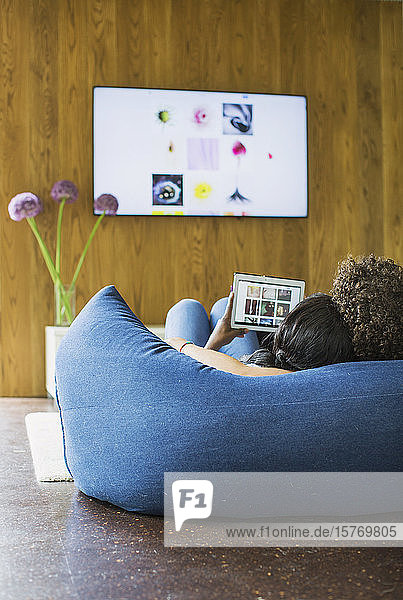 Young couple streaming photos from digital tablet to TV