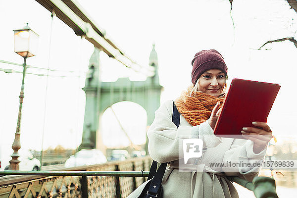 Young woman in stocking cap and scarf using digital tablet on urban bridge