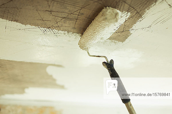 Paint roller painting ceiling white
