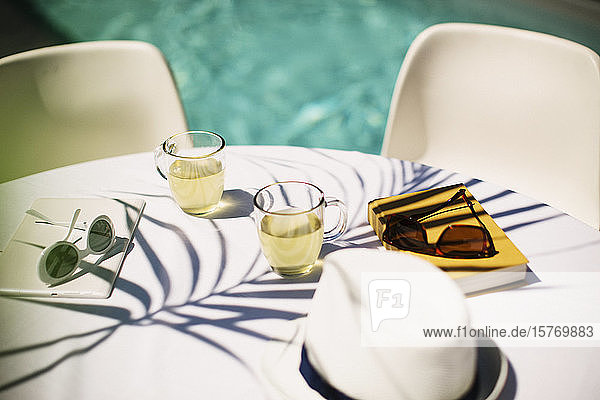 Tea and sunglasses on sunny poolside table