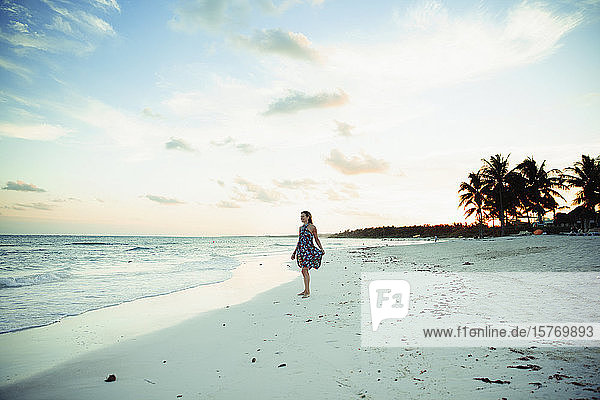 Carefree woman in sun dress on tropical ocean beach Mexico