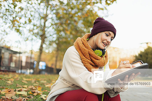 Young woman writing in journal in autumn park