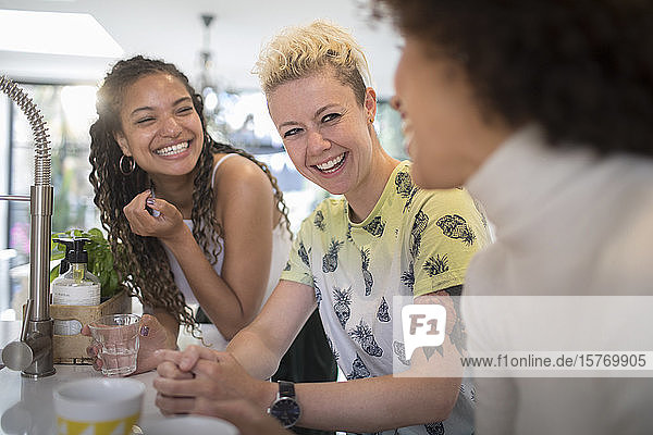 Happy young women friends laughing and talking in kitchen