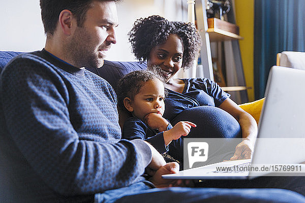 Young pregnant family using laptop on sofa